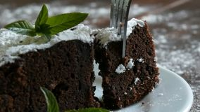 Домодельный испеченный торт пирожного шоколада закутанный с напудренным сахаром на белой плите украшенной с листьями мяты вилка акции видеоматериалы