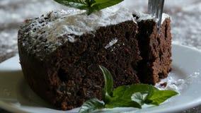 Домодельный испеченный торт пирожного шоколада закутанный с напудренным сахаром на белой плите украшенной с листьями мяты Вилка сток-видео