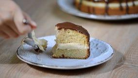 Домодельный кремовый пирог boston, кусок пирога заполненный с заварным кремом и замороженный с шоколадом Девушка есть кремовый пи сток-видео