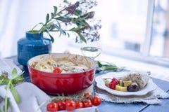 Домодельный обедающий мяса и томатов Таблица около окна и бокала вина голубая ваза цветков стоковое изображение rf