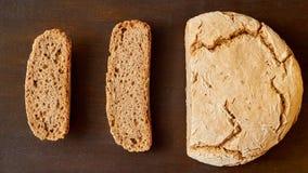 Домодельный отрезанный свежий хлеб на деревянной предпосылке готовой для еды Как раз испеченный вокруг хлеба на коричневой таблиц Стоковая Фотография
