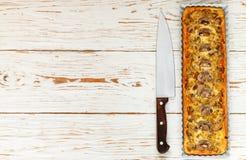 Домодельный пирог с грибами, лук-пореем, сыром и тимианом на белой деревенской предпосылке Традиционный торт закуски и нож на таб стоковая фотография rf
