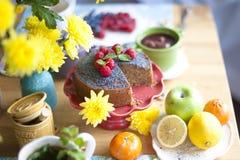 Домодельный пирог с маковыми семененами и полениками Очень вкусный завтрак на таблице и желтых цветках Взгляд сверху Стоковые Фото
