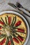 Домодельный пирог с томатами и зелеными фасолями на красивой плите на винтажных таблице, ложке и вилке стоковая фотография rf