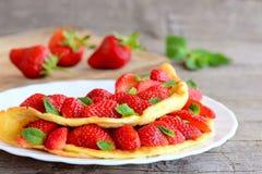 Домодельный пушистый сладостный омлет с клубниками и украшенный с листьями мяты Очень вкусный и здоровый сладостный десерт омлета Стоковое фото RF