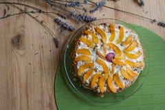 Домодельный торт украшенный с частями зрелых персиков и слив и высушенных цветков лаванды на деревянном столе Стоковое Изображение RF