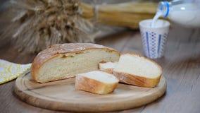 Домодельный хлеб, молоко и зрелые уши рож на деревянной предпосылке акции видеоматериалы