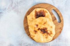 Домодельный хлеб на деревянной доске над голубой предпосылкой стоковое фото