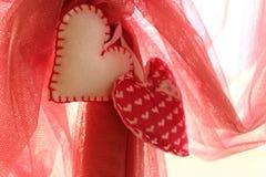 2 домодельных белых и красных сердца против красного vail как предпосылка влюбленности Стоковое Изображение RF