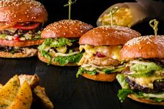 4 домодельных гамбургера на деревянном столе Плюшки с семенами сезама, бургерами говядины и различными ингридиентами Стоковые Изображения