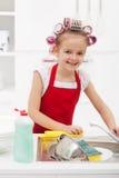 Домоустройство маленькой девочки - делать блюда стоковая фотография rf