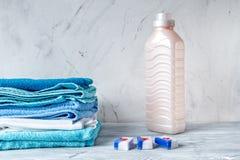 Домоустройство установило с полотенцами и пластичными бутылками на модель-макете предпосылки прачечной Стоковые Фото