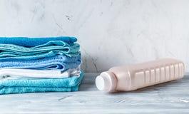 Домоустройство установило с полотенцами и пластичными бутылками на модель-макете предпосылки прачечной Стоковая Фотография