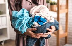 Домохозяйка аккуратно держит кучу одежд стоковые фотографии rf