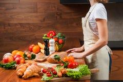Домохозяйка в кухне около таблицы вполне с едой стоковая фотография rf