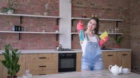 Домохозяйка в прозодеждах и перчатках джинсовой ткани с ветошью и очи акции видеоматериалы