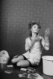 Домохозяйка в curlers волос и резиновых перчатках красит губную помаду губ стоковое фото