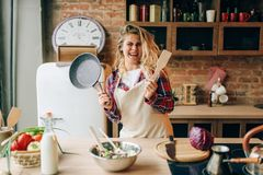 Домохозяйка держа сковороду и деревянный шпатель стоковые фото