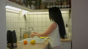 Домохозяйка женщины молодая моя свежие фрукты в кухне под потоком воды, фруктовым салатом подготовки видеоматериал