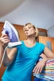 Домохозяйка женщины с утюгом в ее руке стоковые изображения rf