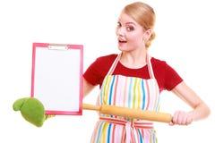 Домохозяйка или кашевар в рисберме кухни держат доску сзажимом для бумаги с пустым пробелом изолированный Стоковое Изображение