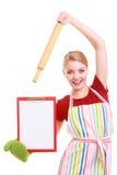 Домохозяйка или кашевар в рисберме кухни держат доску сзажимом для бумаги с пустым пробелом изолированный Стоковые Изображения RF