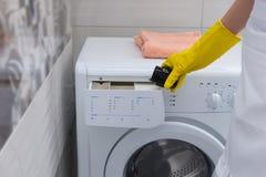 Домохозяйка кладя умягчитель в стиральную машину Стоковые Фото
