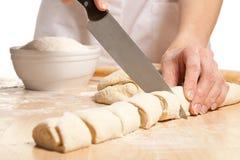 Домохозяйка режа сладостные крены на деревянной доске Стоковое фото RF