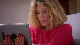 Домохозяйка съемки конца-вверх регулируя волосы говоря в videochat на планшете и дуя поцелуй мило в уютном доме сток-видео