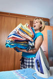 Домохозяйка с большим стогом полотенец для утюжить стоковая фотография