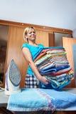 Домохозяйка с большим стогом полотенец для утюжить стоковые изображения rf