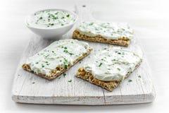 Домодельная здравица Crispbread с плавленым сыром и петрушкой на белой предпосылке деревянной доски Стоковое Изображение RF