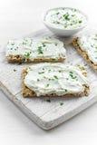 Домодельная здравица Crispbread с плавленым сыром и петрушкой на белой предпосылке деревянной доски Стоковые Фото