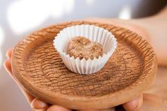 Домодельная конфета с коричневыми карамелькой и гайками молока на плите глины Стоковое Фото