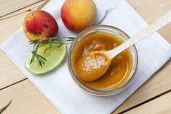 Домодельное варенье абрикоса и свежие абрикосы с листьями Стоковые Фото