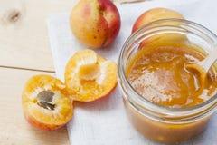 Домодельное варенье абрикоса и свежие абрикосы с листьями Стоковая Фотография