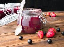 Домодельное варенье с ягодами и ложкой на деревянном столе Стоковая Фотография