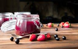 Домодельное варенье с ягодами и ложкой на деревянном столе Стоковое Изображение RF