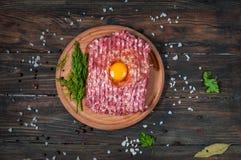 Домодельное сырцовое семенить мясо с яичком и травами крупным планом, взгляд сверху Стоковые Изображения