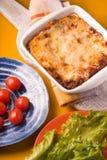 Домодельные лазанья мяса и томат, салат на желтой таблице Стоковое Фото