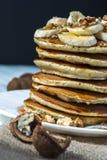 Домодельные блинчики с кусками, медом и грецкими орехами банана на деревянной предпосылке Стоковое Изображение RF