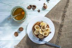 Домодельные блинчики с кусками, медом и грецкими орехами банана на деревянной предпосылке Стоковые Фотографии RF