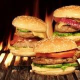 Домодельные гамбургеры на горячем пламенеющем гриле BBQ Стоковые Фотографии RF
