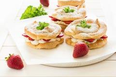 Домодельные кольца печенья choux с сливк и клубниками творога украсили листья мяты Стоковое Изображение RF