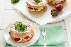 Домодельные кольца печенья choux с сливк и клубниками творога украсили листья мяты Стоковое Фото
