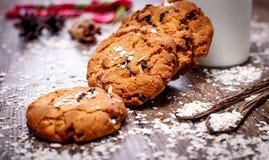 Домодельные печенья овсяной каши с гайками, изюминками, тросточкой конфеты и бутылкой молока на темной деревянной предпосылке, кр Стоковое Изображение RF