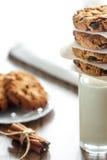 Домодельные печенья овсяной каши с гайками и изюминками и стеклом молока на темной деревянной предпосылке, крупном плане, селекти Стоковая Фотография RF
