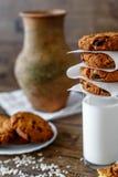 Домодельные печенья овсяной каши с гайками и изюминками и стеклом молока на темной деревянной предпосылке, крупном плане, селекти Стоковое Изображение