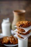 Домодельные печенья овсяной каши с гайками и изюминками и стеклом молока на темной деревянной предпосылке, крупном плане, селекти Стоковое Изображение RF