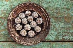 Домодельные сырцовые помадки vegan в shavings кокоса в керамической плите o Стоковое Изображение RF